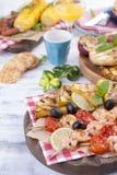 Picknick med grillad mat Korvar och havre på grillfest, räka, grönsaker och frukter Läcker sommarlunch- och plast-disk royaltyfri bild