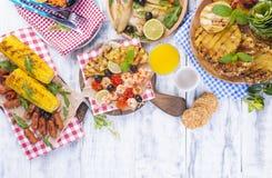 Picknick med grillad mat Korvar och havre på grillfest, räka, grönsaker och frukter Läcker sommarlunch- och plast-disk arkivfoton