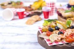 Picknick med grillad mat Korvar och havre på grillfest, räka, grönsaker och frukter Läcker sommarlunch- och plast-disk arkivfoto