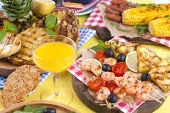 Picknick med grillad mat Korvar och havre på grillfest, räka, grönsaker och frukter Läcker sommarlunch- och plast-disk royaltyfri foto