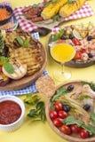 Picknick med grillad mat Korvar och havre på grillfest, räka, grönsaker och frukter Läcker sommarlunch- och plast-disk arkivbild