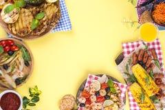Picknick med grillad mat Korvar och havre på grillfest, räka, grönsaker och frukter Läcker sommarlunch- och plast-disk royaltyfria foton