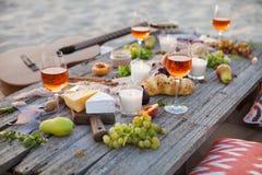 Picknick på stranden på solnedgången i den conc bohostil, mat och drinken Arkivbilder