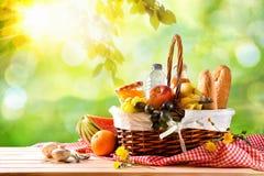 Picknick rieten mand met voedsel op lijst op het gebied royalty-vrije stock afbeeldingen