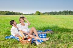Picknick - romantisches Paar in den sonnigen Wiesen Lizenzfreies Stockbild