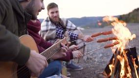 Picknick van jongeren met vuur en kokende worsten op de bergen in de avond Vrolijke vrienden die liederen zingen stock videobeelden
