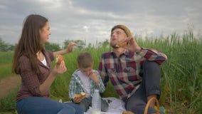 Picknick, vrolijke vrouwelijke de mensenbroodjes van voerbroodjes terwijl het ontspannen met de melkdrinker van de jong geitjejon stock videobeelden