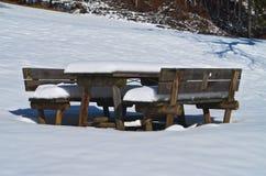 Picknickbank en lijst die door sneeuw wordt behandeld Stock Foto