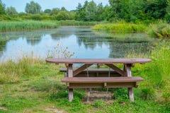 Picknickbank in het landelijke plaatsen naast een meer Stock Fotografie