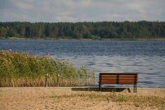 Picknickbänken för vilar på en strand i höst - den provinsiella tysta sjön parkerar Royaltyfria Bilder