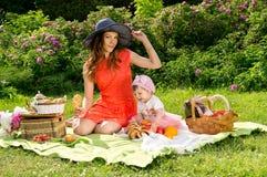 Picknicken mamma och behandla som ett barn på naturen Fotografering för Bildbyråer
