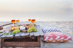 Picknicken Sie auf dem Strand bei Sonnenuntergang in boho Art, Lebensmittel und trinken Sie conc Lizenzfreie Stockbilder