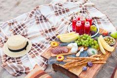 Picknicken Sie auf dem Strand bei Sonnenuntergang im Stil des boho Konzept outd Stockfotografie