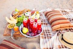 Picknicken Sie auf dem Strand bei Sonnenuntergang im Stil des boho Konzept outd Stockfotos