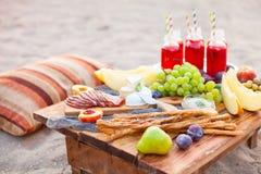 Picknicken Sie auf dem Strand bei Sonnenuntergang im Stil des boho Konzept outd Lizenzfreie Stockbilder