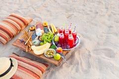 Picknicken Sie auf dem Strand bei Sonnenuntergang im Stil des boho Konzept outd Stockbild