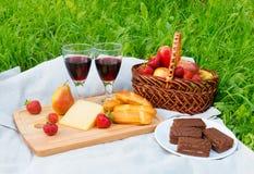 Picknicken Sie mit Rotwein, Brot, Käse, Schokoladenkuchen und Früchten Lizenzfreies Stockfoto