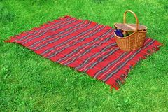 Picknickfilt och korg på gräsmattan Royaltyfria Bilder
