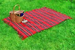 Picknickfilt och korg på gräsmattan Arkivfoto