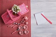 Picknickkarte mit Gedeck und Schneeglöckchen, Tafelsilber, rote weiße überprüfte Serviette stockfotografie
