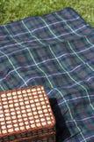 Picknickkorb auf Decke Stockfotografie