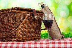 Picknickkorb auf dem Tisch mit Glas des Weins und der Flasche Stockfoto