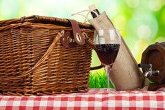 Picknickkorb auf dem Tisch mit Glas Wein Lizenzfreie Stockbilder