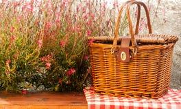 Picknickkorb auf dem Tisch mit roten Blumen Stockbild