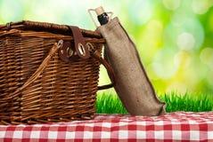 Picknickkorb auf dem Tisch und Weinflasche Stockbilder