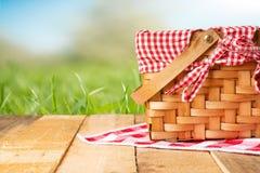Picknickkorb auf einem Holztisch mit einer Tischdecke Entspannung auf einem Picknick und erfreulich in der Natur, mit Raum stockfotografie