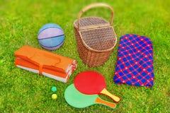 Picknickkorb, -decke, -Racquetball und -ball im Gras Lizenzfreie Stockfotos