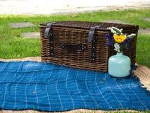 Picknickkorb und -blume auf Gras Stockfotos