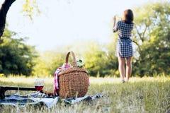 Picknickkorg och flicka i bakgrund Arkivbild