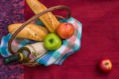 Picknickkorg på den bästa sikten för röd filt Äpplen vitt vin Royaltyfri Foto