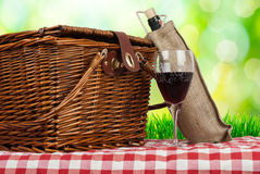 Picknickkorg på tabellen med exponeringsglas av vin och flaskan Arkivfoto