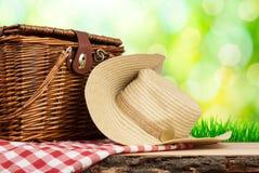 Picknickkorg på tabellen med hatten Arkivfoton