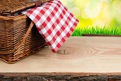 Picknickkorgen på tabellen med kontrollerat beklär Arkivbilder