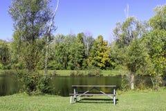 Picknicklijst door een vijver in de herfst stock foto