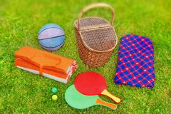 Picknickmand, deken, racketball en bal in het gras Royalty-vrije Stock Foto's