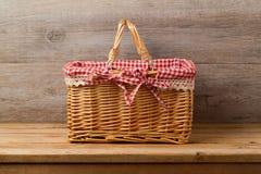 Picknickmand met gecontroleerde doek op lijst Royalty-vrije Stock Afbeeldingen