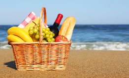 Picknickmand met voedsel op strand stock fotografie
