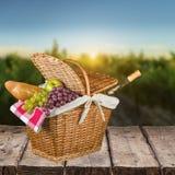 Picknickmand met wijn en vruchten op lijst stock foto's