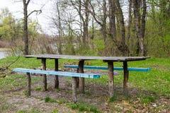 Picknickstandortholztisch und -bänke in Forest Park Stockfotografie
