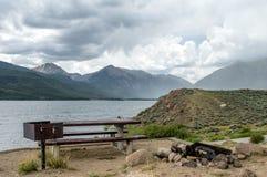 Picknicktabell bredvid sjön Arkivfoto