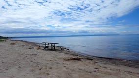 Picknicktabell längs härlig sandstrandkust Dag Sunny Vacation Shoreline Beach Destination i sommar med härlig himmel stock video