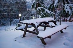 Picknicktabell och bänkar för snö dold under vinter Arkivfoto