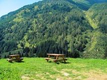 Picknicktabell som är borttappad i panorama- och avslappnande sikten den berg, Royaltyfria Foton