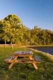 Picknicktabelle durch szenischen See Lizenzfreie Stockbilder