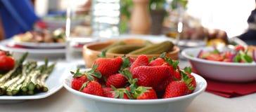 Picknicktabelle mit gegrillten Nahrungsmitteln und Erdbeeren Lizenzfreies Stockfoto