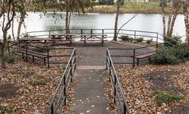 Picknicktabeller bredvid en sjö för lunchavbrott Royaltyfri Fotografi